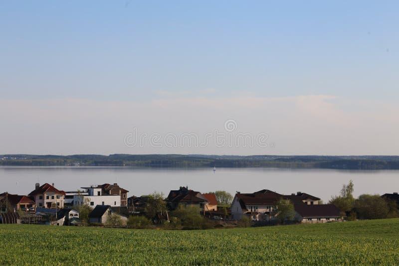 Cottages sur le fond de l'eau et du ciel, dans le premier plan une herbe verte Village Laporovichi, réservoir de Zaslavskoe, repé photographie stock