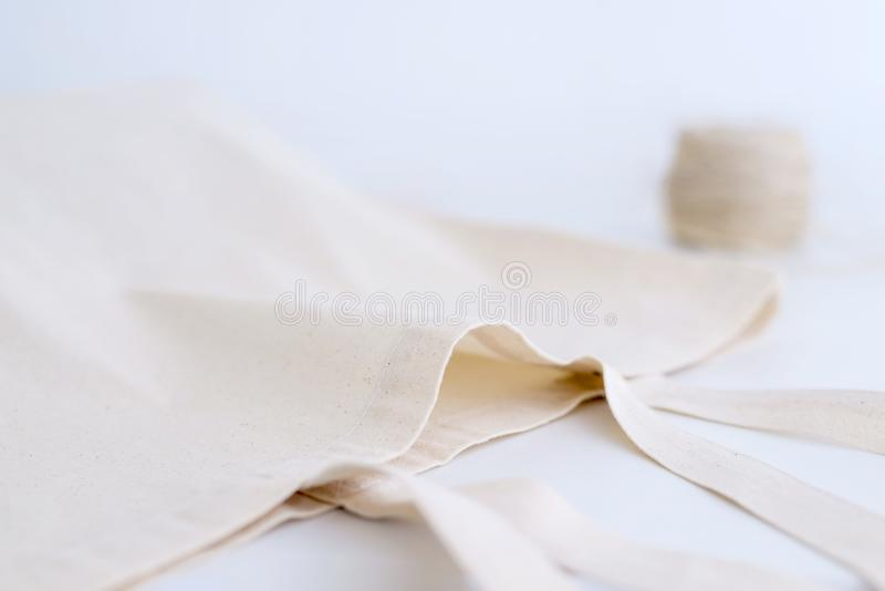 Cotton bag and coil of rope on white stock photography