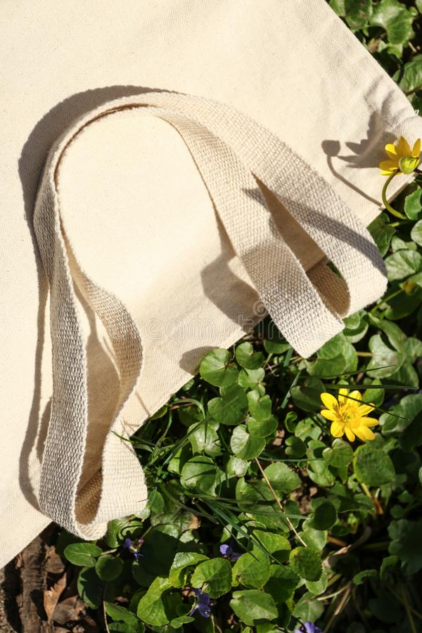 Cotton bag on grass outdoors. Top view stock photography