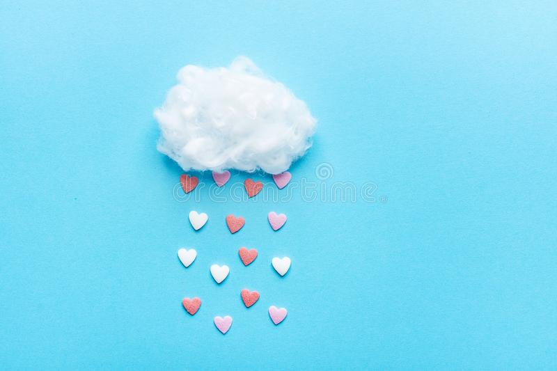 Cotton Ball Cloud Rain Sugar Candy Sprinkle Hearts Red Pink White on Blue Sky Background. Applique Art Composition Valentines. Cotton Ball Cloud Rain Sugar Candy royalty free stock images