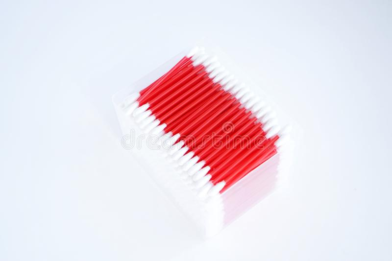 Cotton buds for ears with a red bright stick, in a box, on a white background. Cotton buds ears red bright stick box white background stock photo