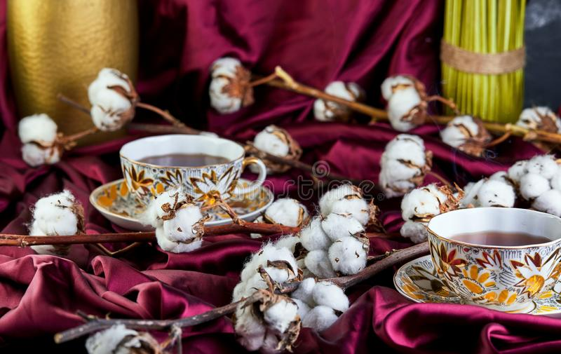 Cotton flowers lying on cloth and cups of tea. The concept royalty free stock photo