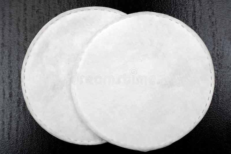 Cotton pads on a black table close-up. Cotton pads on a black table close up, copy space royalty free stock photography