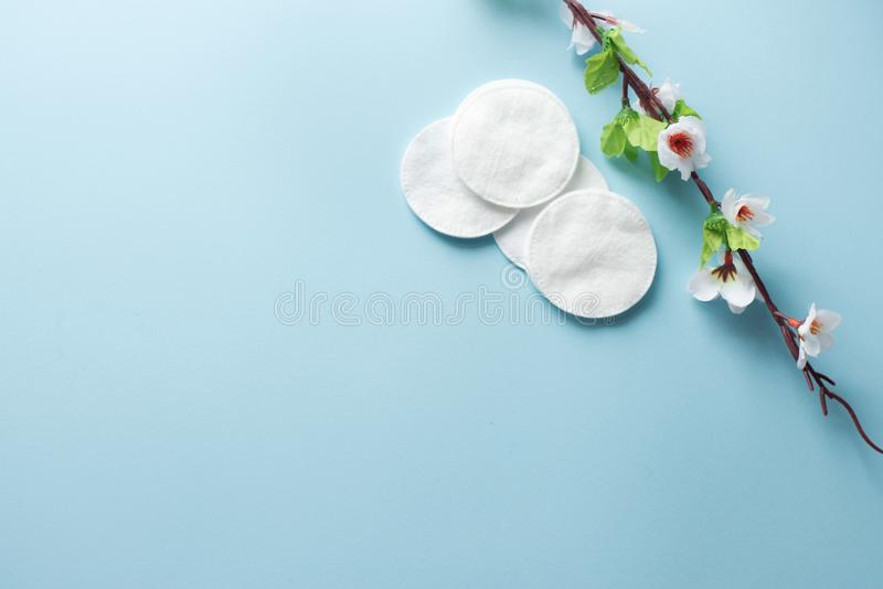 Cotton pads for removal makeup with white flowers on the blue background flatlay.  stock image