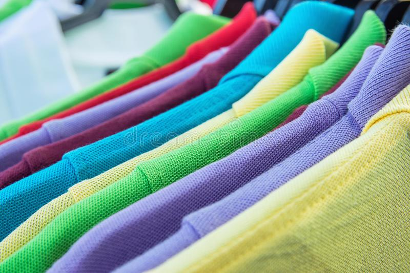 Cotton Polo Shirts of Various Colors Blue Yellow Red Purple Green White Hanging on Hangers on Rack in Clothing Store. Sales Retail royalty free stock photography