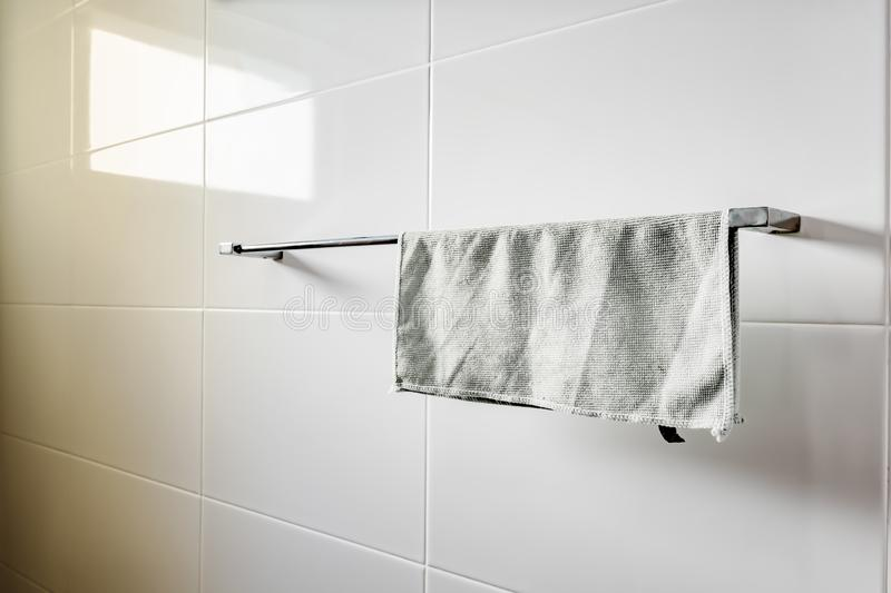 Cotton towel vintage or modern style on the towel rail at white ceramic tile wall stock photography