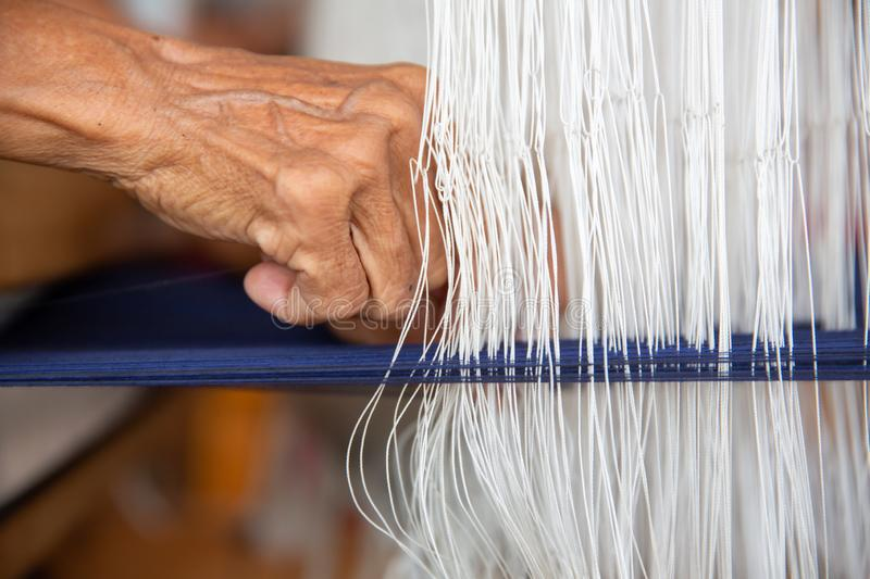 Cotton weaving. Close-up woman hand weaving cotton on manual loom. Thai cotton handmade. Homespun fabric process. The process of stock images