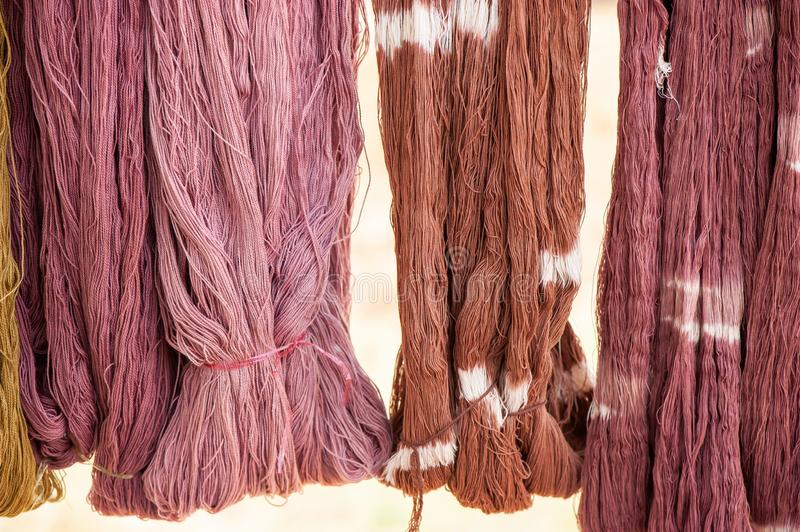 Cotton yarn dyeing with the natural dyes hanging in sunlight for drying. Local handmade products of Sakon Nakhon Province, stock photo