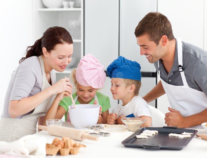 Cottura adorabile della famiglia insieme immagine stock