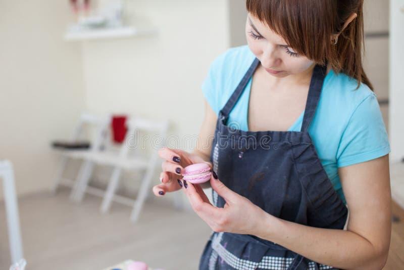 Cottura, alimento e concetto bollente - cuoco unico con la borsa della confetteria che schiaccia crema che riempie ai macarons le immagini stock