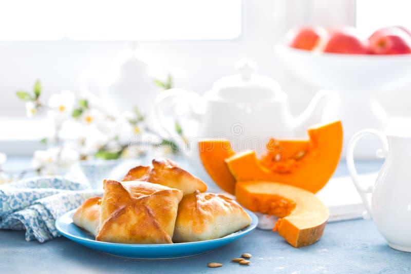 Cottura casalinga deliziosa Tortini con la zucca fresca su fondo bianco immagine stock