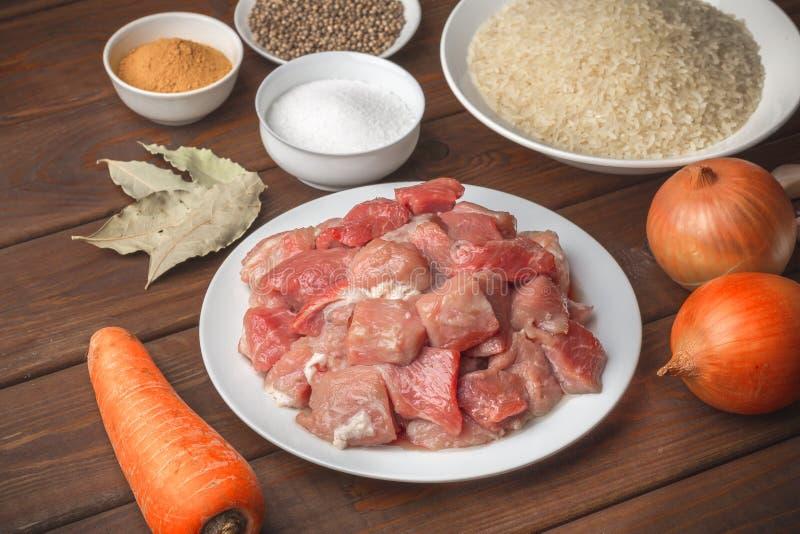 Cottura degli ingredienti Carne cruda affettata, riso, spezie, aglio, carota, cipolla, baia immagini stock