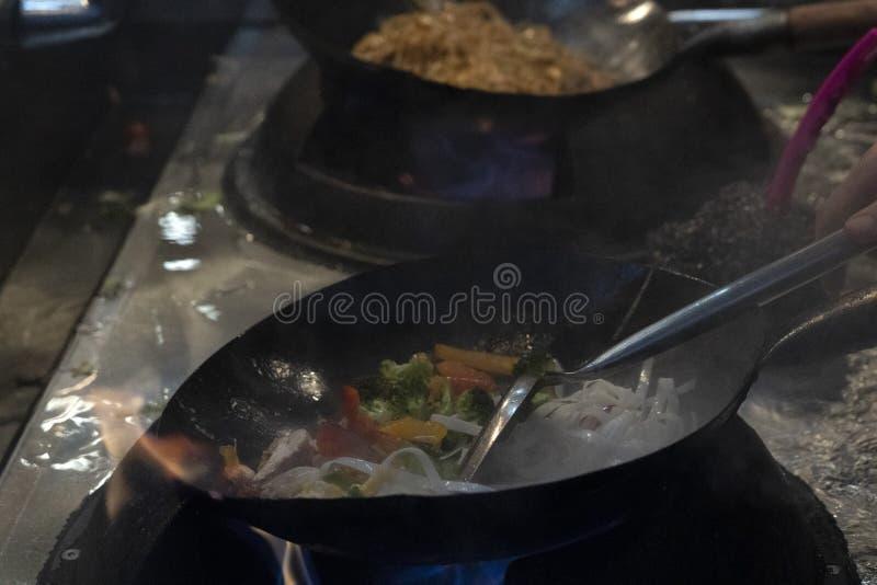 Cottura degli spaghetti del riso del wok immagini stock libere da diritti