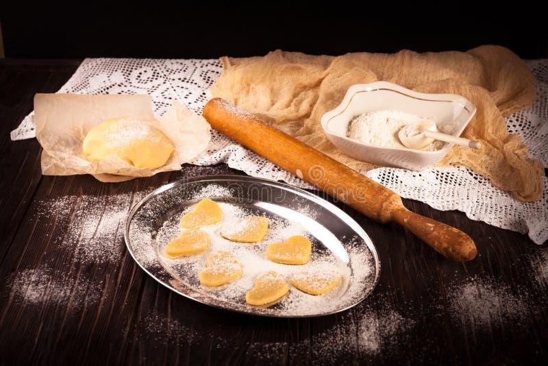 Cottura dei biscotti nel cuore di forma su fondo marrone di legno immagine stock