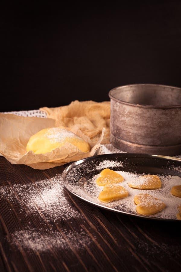 Cottura dei biscotti nel cuore di forma su fondo marrone di legno fotografia stock libera da diritti
