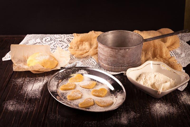 Cottura dei biscotti nel cuore di forma su fondo marrone di legno fotografie stock libere da diritti