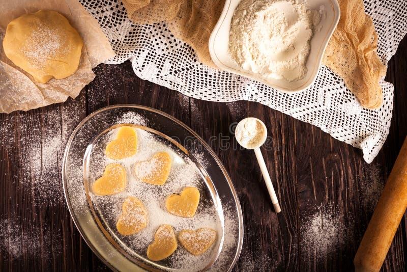 Cottura dei biscotti nel cuore di forma su fondo marrone di legno immagini stock libere da diritti