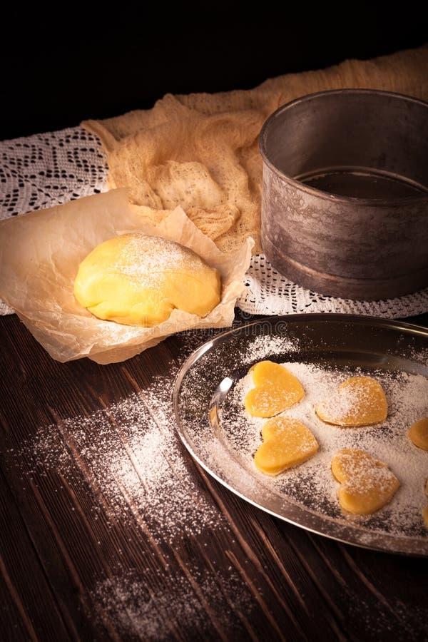 Cottura dei biscotti nel cuore di forma su fondo marrone di legno fotografie stock