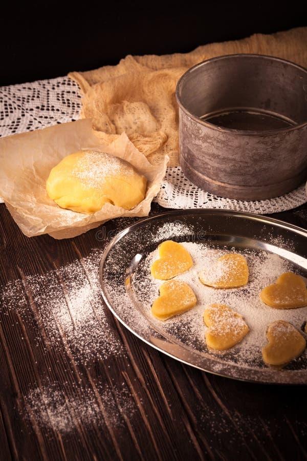Cottura dei biscotti nel cuore di forma su fondo marrone di legno immagini stock