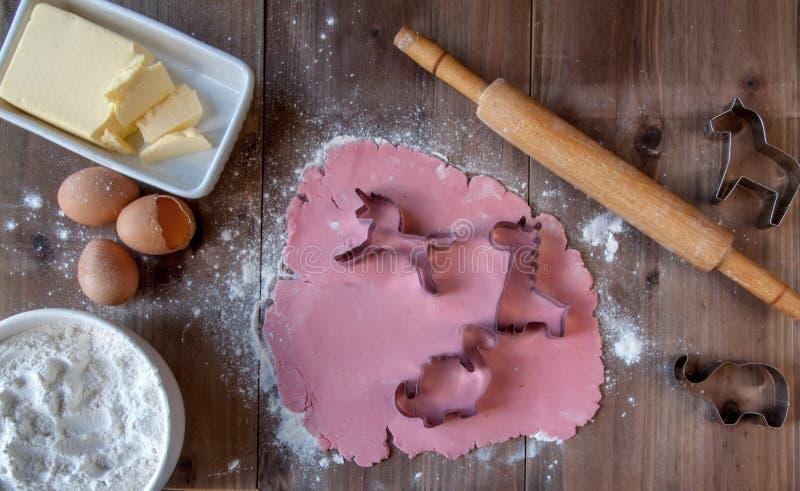 Cottura dei biscotti rosa sotto forma degli animali come regalo per una bambina fotografia stock