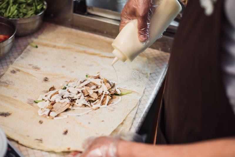 Cottura dei fajitos nel caffè Cottura dello shawarma in pita nella cucina Avvolga il pollo, le carote, pomodoro in pane della pit immagine stock