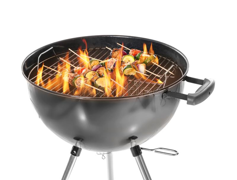 Cottura dei kebab deliziosi sulla griglia del barbecue contro fondo bianco immagine stock