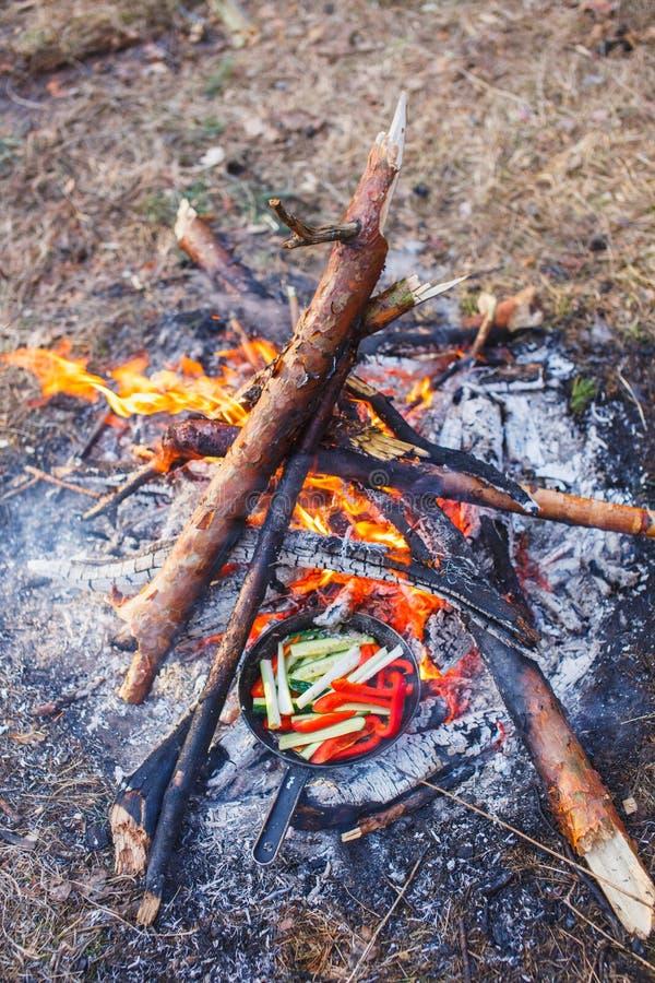 Cottura dei piatti dai peperoni dolci e dai cetrioli rossi in una pentola su un fuoco fotografie stock libere da diritti
