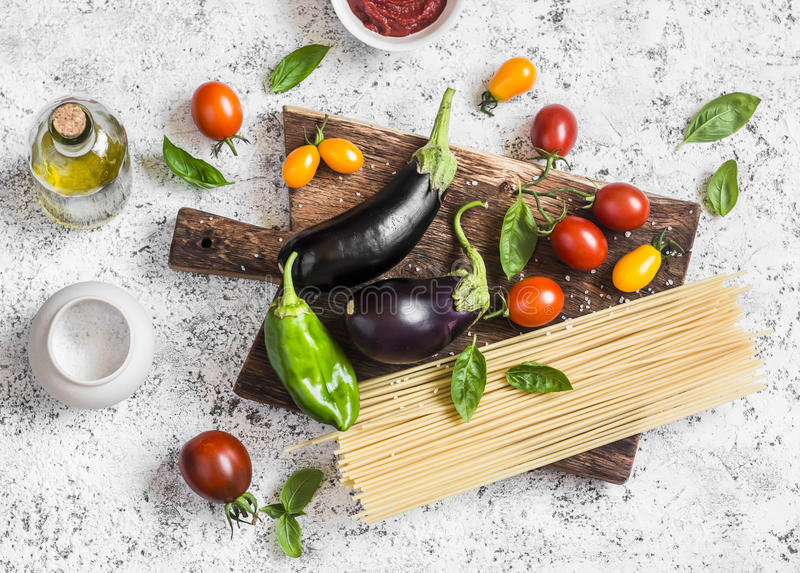 Cottura del fondo Ingredienti crudi per produrre pasta - spaghetti, melanzana, pomodori, pepe, olio d'oliva, salsa al pomodoro e  fotografia stock