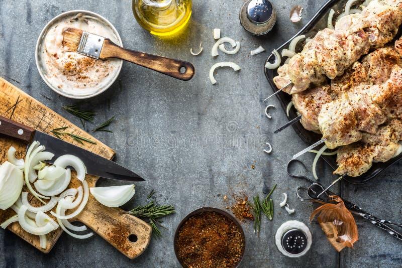 Cottura del kebab in salsa e spezie della marinata, carne cruda marinata sugli spiedi fotografia stock libera da diritti