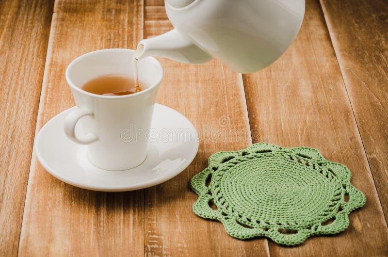 Cottura del tè in una tazza bianca con una teiera/una cottura del tè in una tazza bianca con una teiera su un fondo di legno Fuoc immagini stock