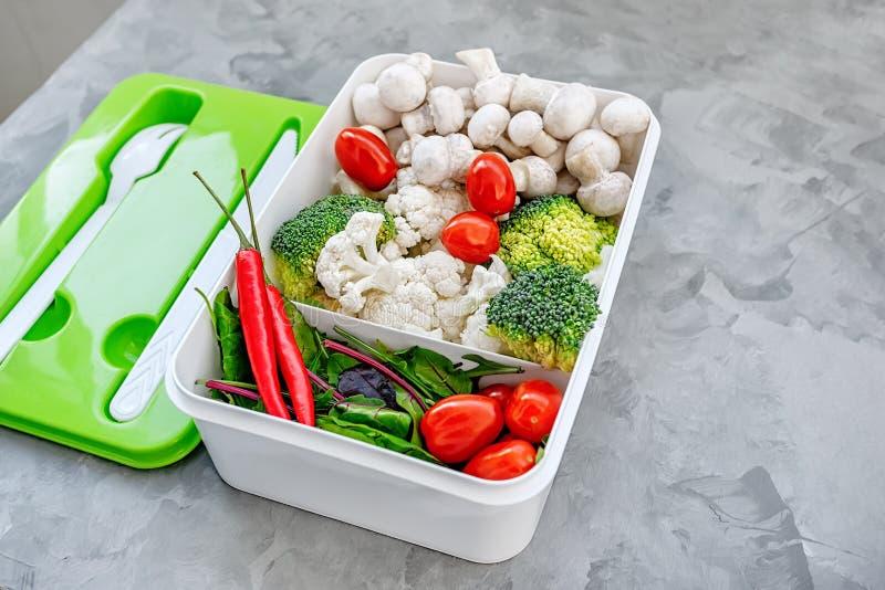 Cottura dell'alimento del vegano con le verdure crude Broccoli e cavolfiore, pepe e funghi prataioli per una legumiera in una pla fotografia stock