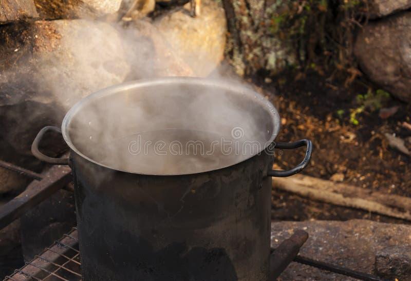 Cottura dell'alimento nella natura Grande vaso su fuoco in foresta immagine stock