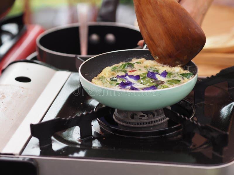 Cottura dell'omelette con le verdure, erbe sulla pentola immagini stock libere da diritti