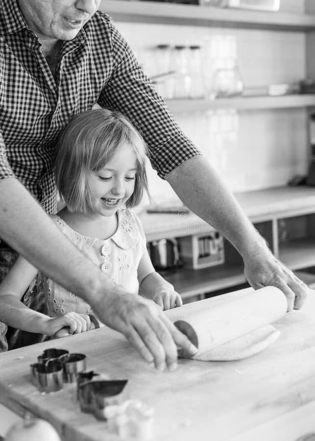 Cottura della bambina che fa il padre Activity Concept dei biscotti fotografia stock