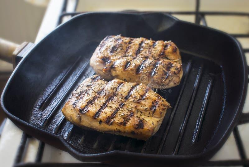 Cottura della bistecca del pollo sulla leccarda Alimento sano immagine stock