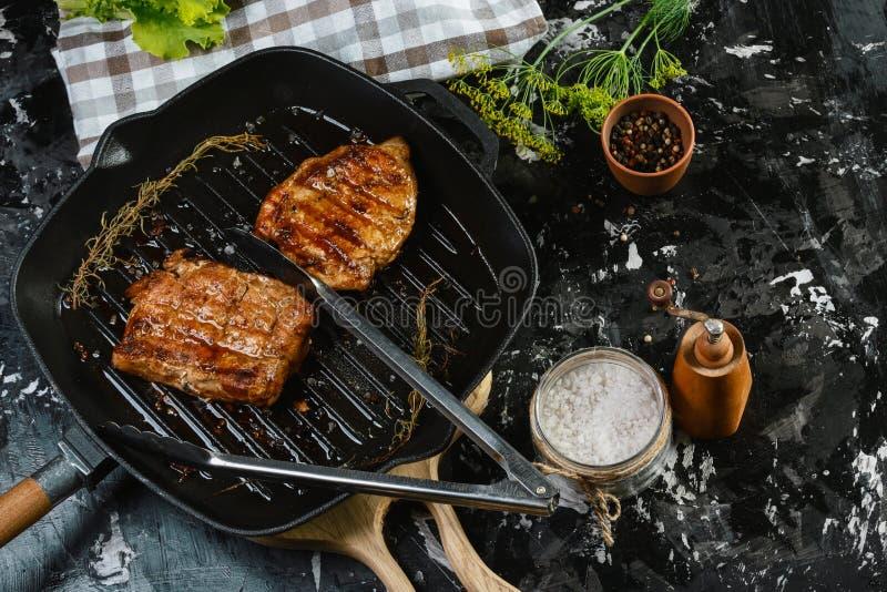 Cottura della bistecca dell'occhio della costola con le erbe sulla leccarda con i rosmarini ed il sale marino Immagine autentica  immagini stock