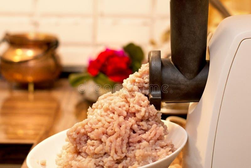 Cottura della carne tritata in una tritacarne elettrica sul tavolo da cucina fotografia stock