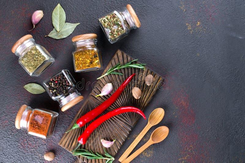 Cottura della tavola con le spezie in barattoli ed erbe di vetro su buio fotografie stock libere da diritti