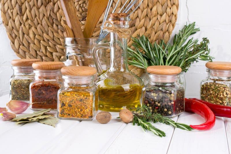 Cottura della tavola con le spezie in barattoli ed erbe di vetro Sulla tabella bianca immagini stock libere da diritti