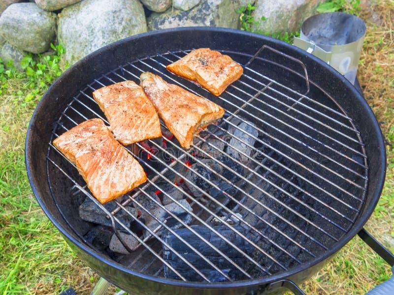 Cottura delle bistecche di color salmone fresche sulla griglia, all'aperto di estate immagini stock