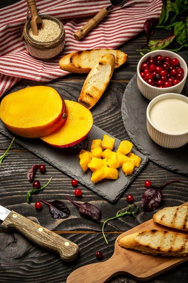 Cottura delle Bruschette con formaggio, mango di Alphonso Bruschetta con il mango ed il formaggio casalingo Nutritionon vegetaria fotografia stock libera da diritti