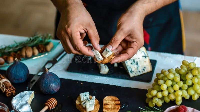 Cottura delle Bruschette con i fichi, il formaggio blu e le noci su pane crostoso arrostito dalle mani del cuoco unico sul bordo  immagini stock libere da diritti