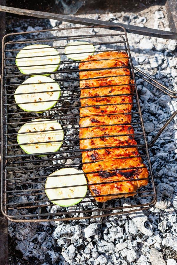 Cottura delle costole di carne di maiale crude con zucca affettata in griglia immagini stock