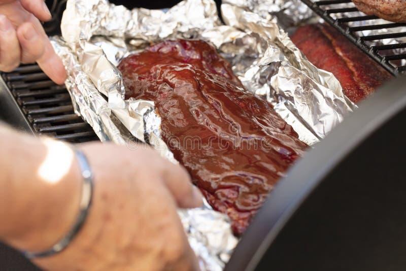 Cottura delle costole di scarsità su una griglia del barbecue fotografie stock libere da diritti