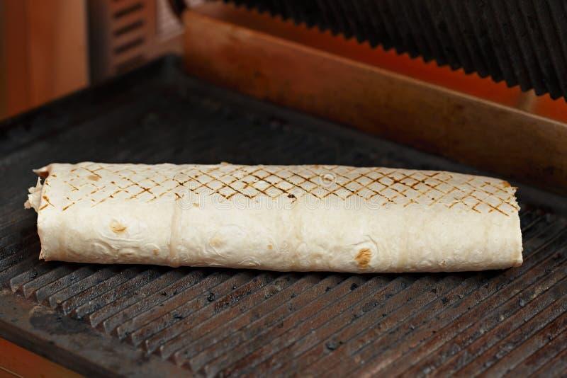 Cottura dello shawarma in pane della pita fotografia stock