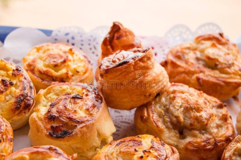Cottura domestica dolce calda fresca sul tovagliolo di carta del pizzo, rotoli dei panini fotografia stock