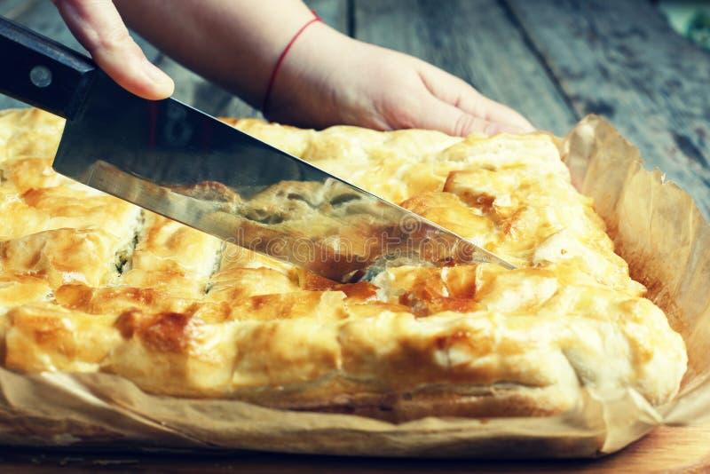 Cottura domestica Le mani del ` s delle donne hanno tagliato la torta casalinga con il riempimento fotografie stock