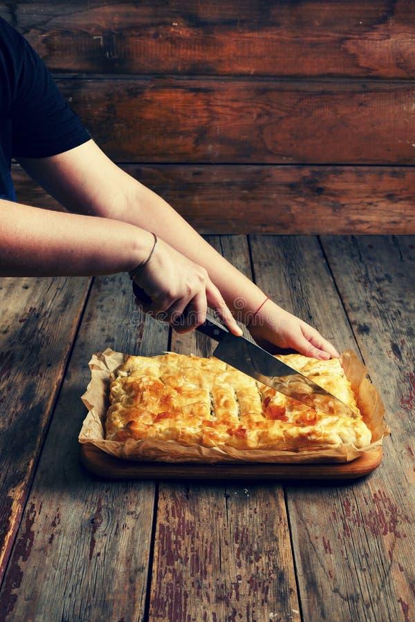 Cottura domestica Le mani del ` s delle donne hanno tagliato la torta casalinga con il riempimento Celebrazione del giorno di ind immagini stock libere da diritti