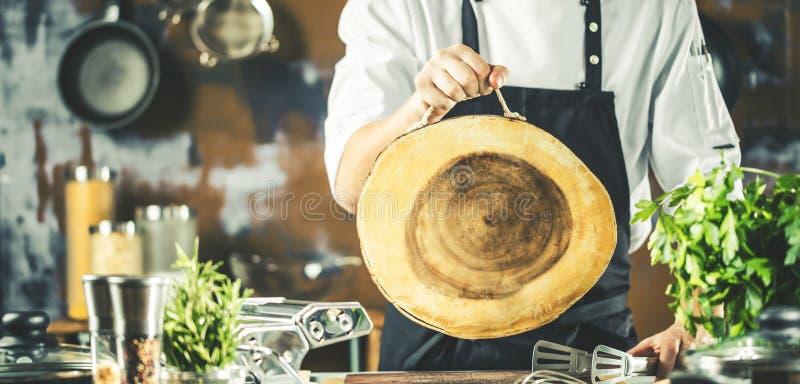 Cottura, professione e concetto della gente - cuoco maschio del cuoco unico che produce alimento alla cucina del ristorante fotografie stock libere da diritti