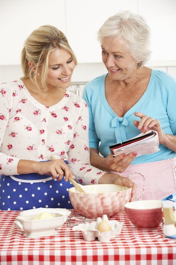 Cottura senior della figlia dell'adulto e della donna nella cucina fotografia stock